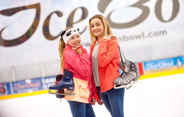 Two Girls with ice skates slung over shoulder at ice rink
