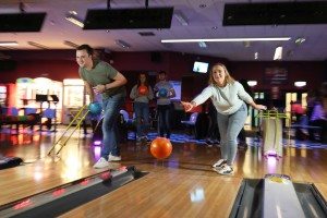 Two people bowling at dimly lit bowling alley