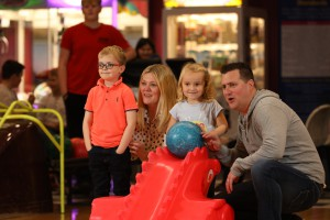 Family playing tenpin bowling