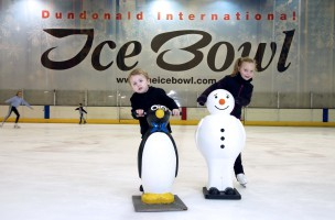 Two kids ice skating with help from penguin and snowman skating aids